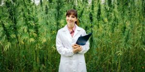 A woman in a lab coat with a clipboard stands in front of a cannabis field.