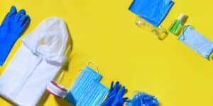 Folding medical protective clothing uniform, masks, glasses and sanitizer on yellow background.